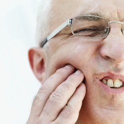 Man pressing into his jaw with a look of pain