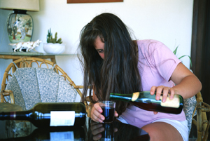 Woman pours wine in large glass from wine bottle, another empty bottle lays on the table next to her.