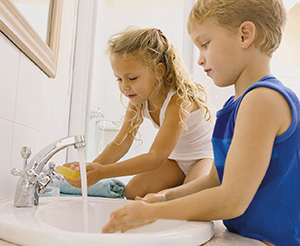 Girl and boy washing hands in sink.