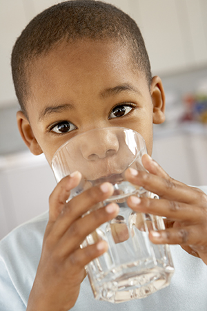 Boy drinking glass of water.
