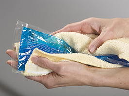 Closeup of hands wrapping ice pack in towel.