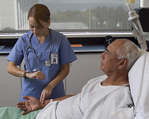 Healthcare provider checking patient's pulse in hospital bed.