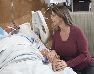 Woman holding hand of man lying in hospital bed.