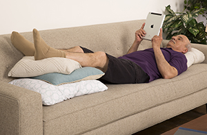 Man lying on couch with legs elevated on pillows.
