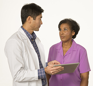 Healthcare provider holding tablet, talking to woman.