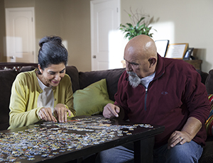 Man and woman doing jigsaw puzzle.