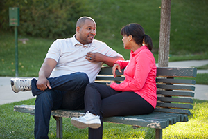 Man and woman sitting on park bench, talking.