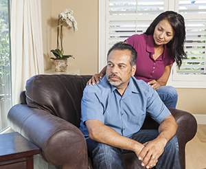 Woman comforting man seated in chair, looking concerned