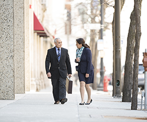 Businessman and businesswoman walking on pavement in city.
