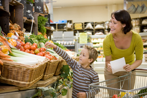 Woman and a small child shopping in produce section of grocery store.