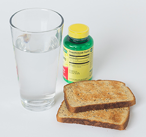 Toast, glass of water, and two pills.