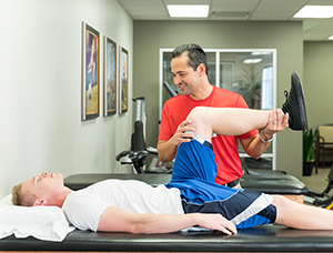 Physical therapist working with man's knee.