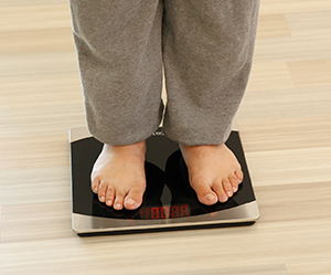 Closeup of woman's feet on bathroom scale.