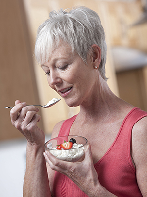 Woman eating cottage cheese and fruit.