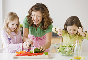 Family making salad in kitchen.