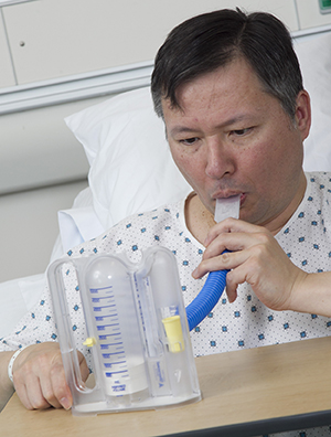 Man using incentive spirometer in hospital bed.