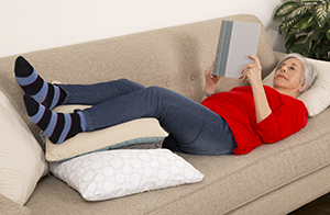 Woman lying on couch with feet raised.