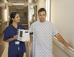 Patient walking in hospital hall with an IV pole and healthcare provider.