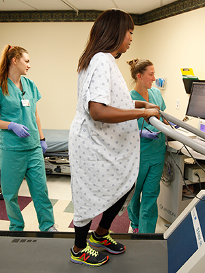 Healthcare providers giving cardiac stress test to woman on treadmill.