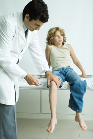 Male healthcare provider checking boy's reflexes.
