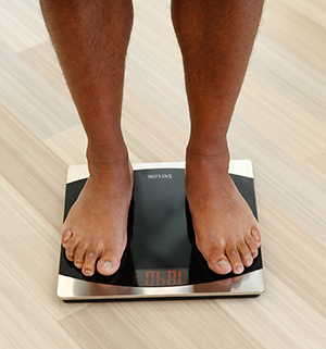 Closeup of man's feet on bathroom scale.