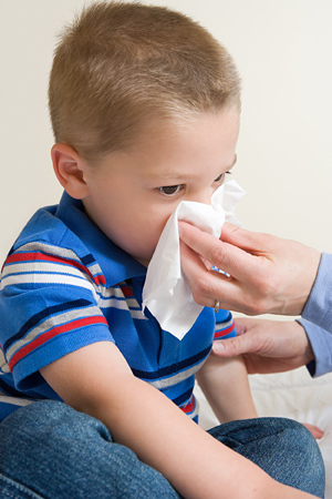 Young boy blowing nose in tissue.