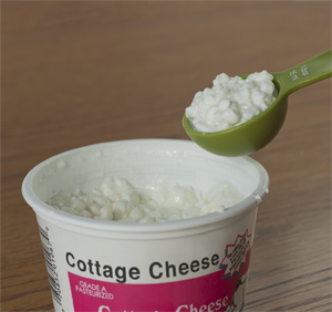 Closeup of tablespoon measuring out cottage cheese.