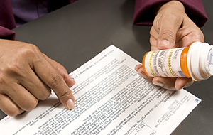 Closeup of hands with prescription information and prescription pill bottle.