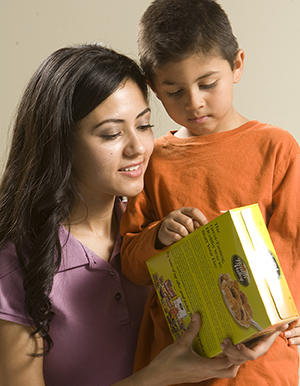 Woman and boy reading label on cereal box.