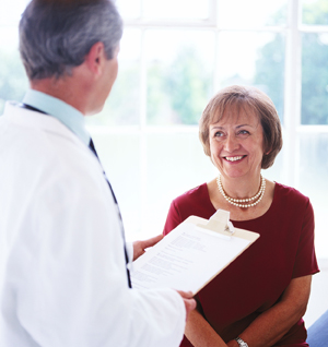 Doctor talking with middle aged female patient.