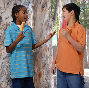 Two boys eating frozen treats.