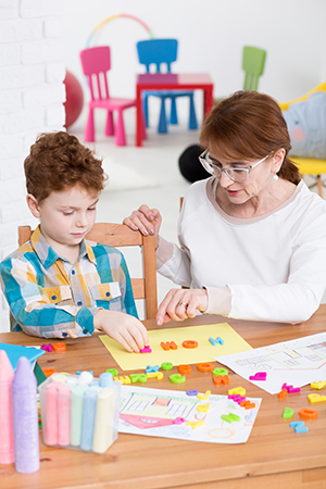 Therapist helping young boy learn the alphabet