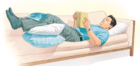 Man lying on couch, reading, with legs supported by pillows. Ice pack is on front of lower legs.
