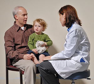 Man and toddler boy talking to healthcare provider.